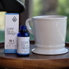 Photo of Care By Design 18:1 sublingual drops on a table aside a tea cup
