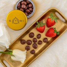 Photo of a tin of Satori chocolates and strawberries and chocolates on a platter